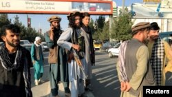塔利班成員站在哈米德·卡爾扎伊國際機場外。(2021年8月16日)