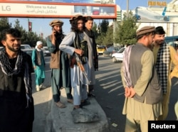 A member of Taliban, center, stands outside Hamid Karzai International Airport in Kabul, Afghanistan, August 16, 2021.
