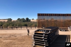 FILE - In this Jan. 10, 2020, photo, people work at a portion of border wall which is under construction in Yuma, Ariz.