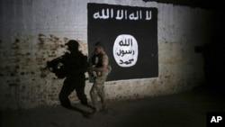 Arhiv, ilustracija - Irački vojnik istražuje tunel ispred grafita sa zastavom terorističke grupe Islamska država.
