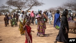 FILE - Refugees walk in a camp for internally displaced persons, in northern Burkina Faso, June 20, 2021.