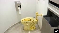 """Toilet 18 karat, berjudul """"Amerika,"""" oleh Maurizio Cattelan di kamar kecil Museum Solomon R. Guggenheim di New York, 16 September 2016. (Foto: AP)"""