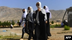 Afghan girl students cover their faces with scarfs as they walk inside the compound of their school after it was reopened, which was earlier closed due to the COVID-19 coronavirus pandemic, in Herat on Aug. 23, 2020.