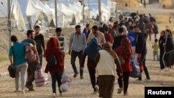 Keluarga-keluarga Suriah yang melarikan diri setelah serangan Turki di Suriah tiba di kamp Bardarash, di pinggiran Dohuk, Irak, 25 Oktober 2019.