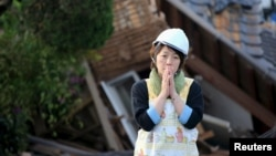 A woman reacts in front of collapsed house caused by an earthquake in Mashiki town, Kumamoto prefecture, southern Japan, in this photo taken by Kyodo, April 16, 2016.