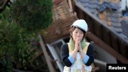 یک زن ژاپنی مقابل یک خانه ویران شده در اثر زمین لرزه در شهر ماشیکی.