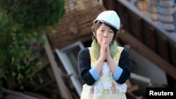 Một người phụ nữ trước ngôi nhà bị sập bởi trận động đất ở thị trấn Mashiki, quận Kumamoto, miền nam Nhật Bản, trong bức ảnh chụp bởi Kyodo, ngày 16 tháng 4 năm 2016.