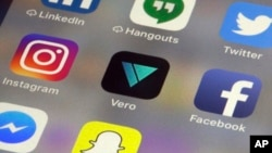 The Vero app, center, is displayed on an iPhone in New York, March 1, 2018. Instagram users fed up with ads, with the end of chronologically displayed posts and the lack of granular privacy controls are flocking to Vero.