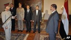Ông Abdel Fattah el-Sissi (trái), vừa được chỉ định làm Bộ trưởng Quốc phòng Ai Cập, tuyên thệ nhậm chức trước Tổng thống Mohammed Morsi hôm 12/8/12