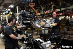 FILE - Chrysler Group LLC assembly workers lower an engine on to the frame of a 2014 Ram 1500 pickup truck on the assembly line at the Warren Truck Plant in Warren, Michigan, Sept. 25, 2014.