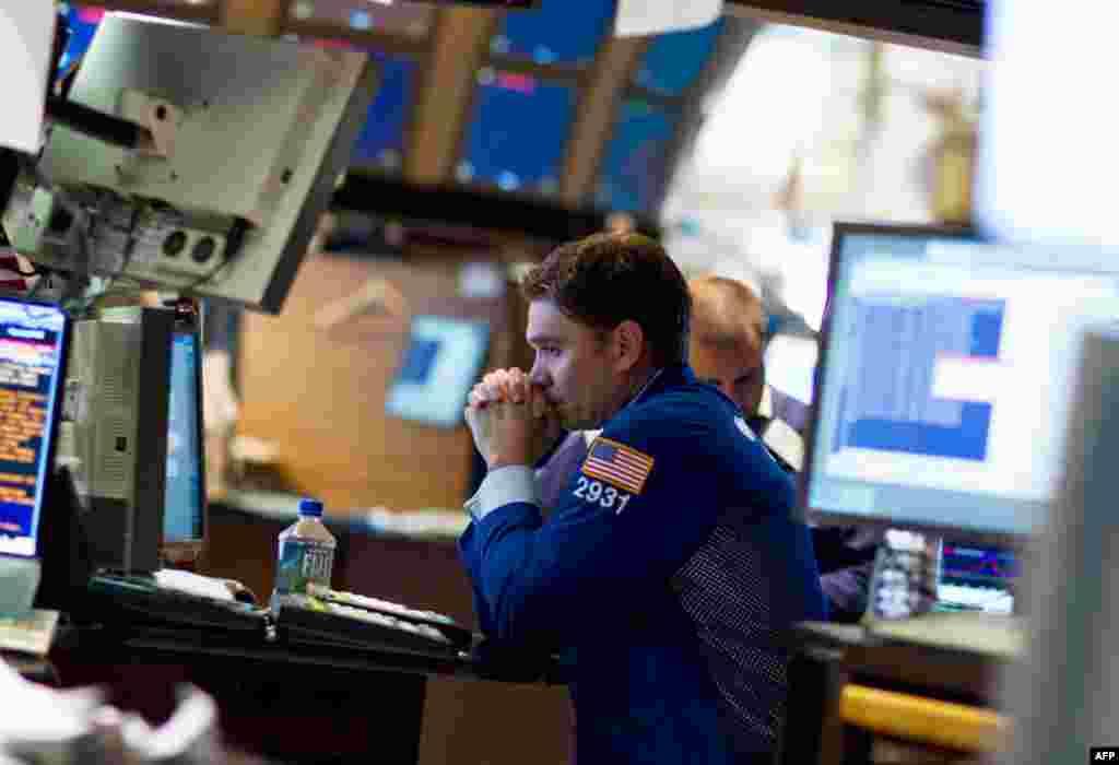 4 tháng 8: Nhân viên giao dịch tại sàn chứng khoán New York vào lúc chỉ số Dow Jones trợt hơn 500 điểm hôm thứ Năm, vụ trợt giá lớn nhất kể từ 22 tháng 10 năm 2008. (AP Photo/Jin Lee)