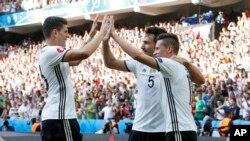 Mario Gomez célèbre avec ses coéquipiers Mats Hummels, au centre, et Julian Draxler, à droite, après un but lors du match de football Euro 2016 de 16 matches entre l'Allemagne et la Slovaquie, au stade Pierre Mauroy à Villeneuve d'Ascq, 2016.