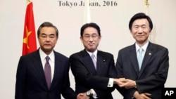 Dari kiri: Menlu China Wang Yi, Menlu Jepang Fumio Kishida, dan Menlu Korsel Yun Byung-se, berpose sebelum pertemuan di Tokyo, Selasa (23/8).