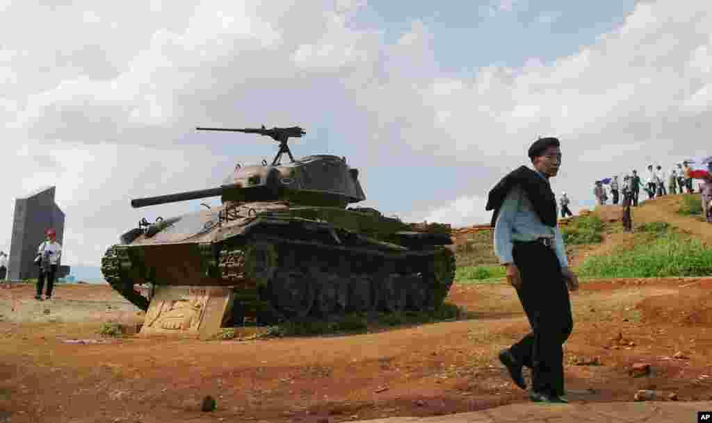 Du khách đi ngang qua một chiếc xe tăng của Pháp bị phá hủy tại di tích của chiến trường trên đồi A1 ở Điện Biên Phủ. (AP Photo/Richard Vogel)