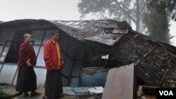 Biksu muda melintasi rumah yang roboh akibat gempa berkekuatan 6.9 di Gangtok, India (19/9).