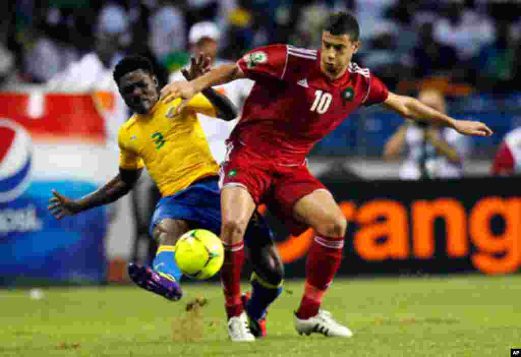 Morocco's Belhanda fights for the ball with Gabon's Mouele during their African Cup of Nations soccer match in Libreville