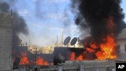 ຮູບພາບຖ່າຍໂດຍປະຊາຊົນ ທີ່ນຳອອກເຜີຍແຜ່ໂດຍຄະນະກຳມະການປະສານງານທ້ອງຖິ່ນໃນຊີເຣຍສະແດງໃຫ້ ເຫັນໄຟພວມໄໝ້ເຮືອນ ທີ່ເມືອງ Homs ຫຼັງຈາກກຳລັງລັດຖະບານ ຍິງໂຈມຕີເຮືອນດັ່ງກ່າວ (22 ກຸມພາ 2011)
