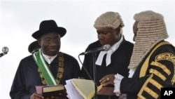 Nigerian President Goodluck Jonathan, left, takes the oath of office before Justice Sunday Olorundanusi, center, and Chief Justice of Nigeria Katsina Alu during his inauguration ceremony at the main parade ground in Nigeria's capital of Abuja Sunday, May