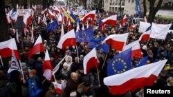 Des manifestants hissant les drapeaux polonais et de l'Union européenne lors d'une manifestation anti-gouvernementale devant la Cour constitutionnelle à Varsovie , en Pologne , le 12 déc 2015. REUTERS/Kacper Pempel - RTX1YD19