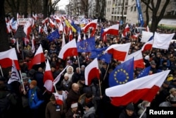 File - People hold European Union and Polish national flags during an anti-government demonstration in front of the Constitutional Court in Warsaw, Poland, Dec. 12, 2015.