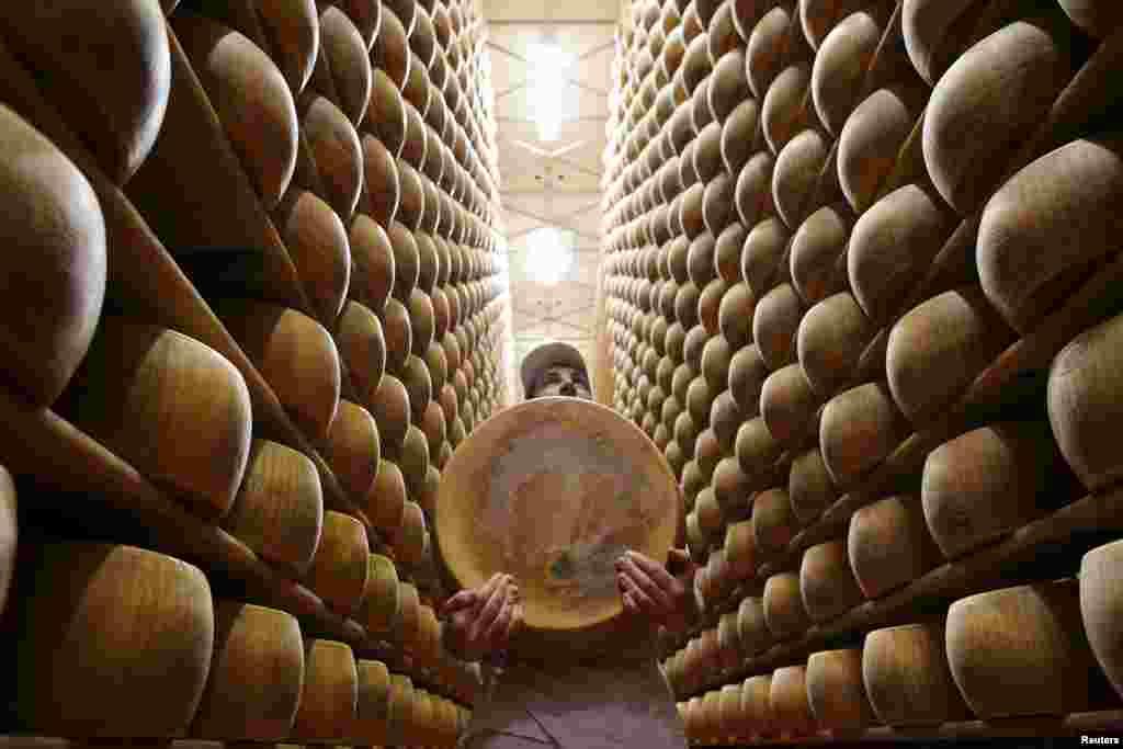 កម្មករម្នាក់លើកហ្វ្រូម៉ា Parmesan ចេញពីធ្នើរក្នុងឃ្លាំងនៅឯរោងចក្រផលិតផលទឹកដោះ Madonne Caseificio dell'Emilia នៅក្រុង Modena ប្រទេសអ៊ីតាលី។