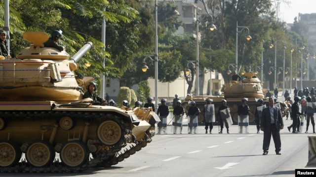Army tanks and riot police are seen outside the presidential palace in Cairo, December 12, 2012.