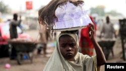 Girl hawks drinking water packed in sachets along street after days of religious clashes in the northern Nigerian city of Maiduguri, Aug. 4, 2009.