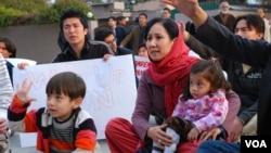 مظاہرے میں ایک خاتون اپنے بچوں کے ہمراہ شریک ہیں