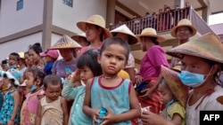 FILE - children and elders displaced from recent fighting between government troops and ethnic rebels in their area, wait for food distribution at a monastery in Namlan town, Myanmar's eastern Shan state, May 25, 2021.