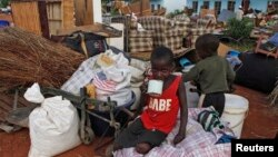 FILE: Zimbabwean children sit among salvaged possessions at a transit camp for over 100 families displaced by floods near the Tokwe-Mukorsi dam about 430km (267 miles) south of Harare, Feb. 13, 2014.