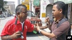 图为马来西亚便衣警察5月1日试图铐走活动人士