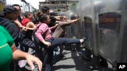 FILE - A woman kicks the shield of a National Guard soldier as other demonstrators push during a protest demanding food, a few blocks from Miraflores presidential palace in Caracas, Venezuela, June 2, 2016.