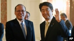 Philippine President Benigno Aquino III, left, and Japan's Prime Minister Shinzo Abe pose for photographers upon Aquino's arrival at the Akasaka State Guesthouse for their meeting in Tokyo, June 4, 2015.