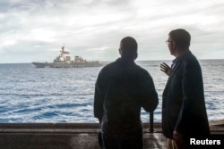 "FILE - U.S. Secretary of Defense Ash Carter, right, speaks with U.S. Navy Cmdr. Robert Francis Jr., as Carter visited the USS Theodore Roosevelt aircraft carrier in the South China Sea. US Ambassador to Asean Nina Hachigian called US freedom of navigation operations ""routine"" and ""lawful."""