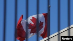 Bendera nasional Kanada berkibar di atas kedutaan Kanada di Beijing, China, 15 Januari 2019. (Foto: Reuters/Thomas Peter)