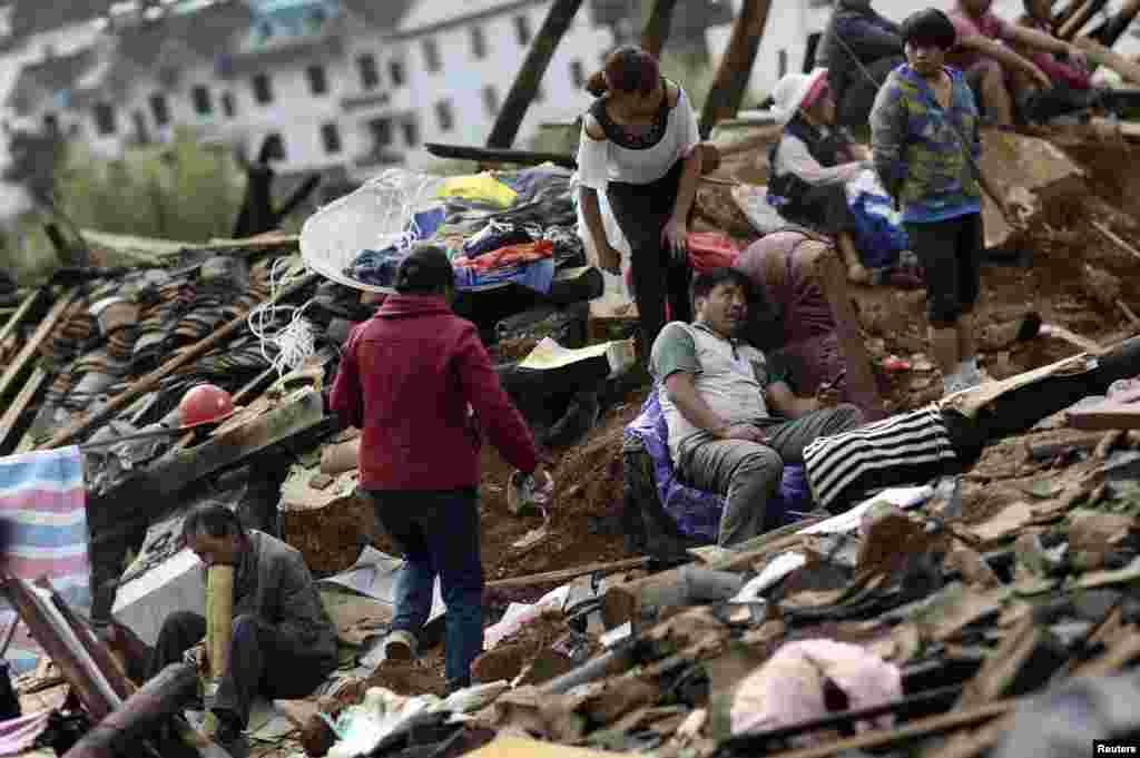 Zəlzələ zamanı evi dağılan ailə - Yunnan vilayəti, Lodian mahalı, 4 avqust, 2014
