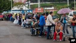 FILE - Patrons line up in a San Cristobal supermarket parking lot in shortage-plagued Venezuela, Jan. 22, 2015