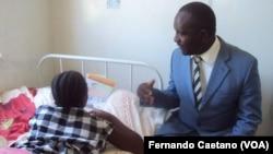 José Augusto, director de Culltura do Kwanza Sul, entrega livro infantil a uma mãe na Pediatria do Sumbe
