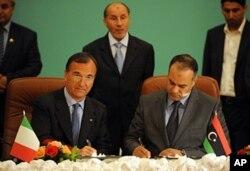 Le ministre italien des Affaires étrangères, Franco Frattini ( à gauche) signant un mémorendum d'entente avec le chef de la diplomatie des rebelles libyens, Ali al-Essawi , à Benghazi