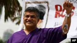 FILE - Malaysian cartoonist Zulkiflee Anwar Alhaque, better known as Zunar, wearing a prison outfit and plastic handcuffs poses for photographers prior to launching his book in Petaling Jaya, Malaysia.