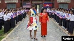 IBM negara AS Michelle Obama (kiri) didampingi ibu negara Kamboja Bun Rany (berbaju merah), mengunjungi SMA Hun Sen Prasaat Bankong di kawasan Siem Reap, 21 Maret 2015 (REUTERS/Athit Perawongmetha)