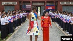 U.S. first lady Michelle Obama (L) walks with Bun Rany, Cambodia's first lady during a visit to promote girls' education at Hun Sen Prasaat Bankong high school on the outskirts of Siem Reap, March 21, 2015.