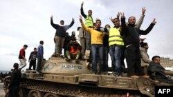 Người biểu tình chống chính phủ làm dấu hiệu chiến thắng trong lúc đứng trên một chiếc xe tăng ở thành phố Benghazi, Libya, ngày 24/2/2011