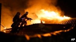 Lính cứu hỏa dập lửa tại một ngôi nhà bị trận pháo kích kéo dài suốt đêm phá hủy ở Donetsk, 16/8/2015.