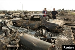 Canadian Prime Minister Justin Trudeau and Fort McMurray Fire Chief Darby Allen, right, look over a burnt out car while visiting neighborhoods devastated by the wildfire that forced the evacuation of the city in Fort McMurray, Alberta, Canada, May 13, 2016.