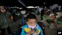 4月9日,在禽流感病毒散播得陰影下安徽一個小童帶上口罩走過一個農場。