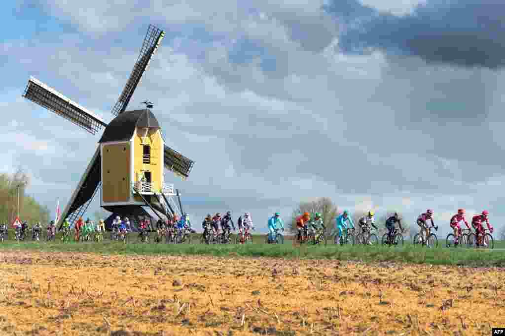 Ciclistas passam junto ao moinho Hubertus durante a Amstel Gold Race em Beek, na Holanda.