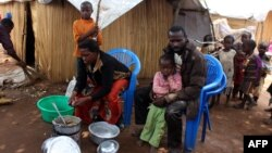 A family of refugees from the Democratic Republic of Congo sit by their makeshift hut at the Kenani refugee transit camp in Nchelenge, Oct. 30, 2017, during a visit by Zambian President Edward Lungu.