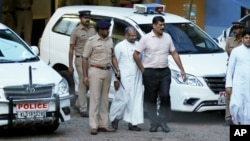 Franco Mulakkal, bishop of the Indian city of Jalandhar, center, whom a nun has accused of rape, leaves after appearing for questioning by police in Kochi, India, Sept. 19, 2018. The bishop has denied the accusation.