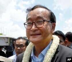 FILE - In this Aug. 16, 2015, file photo, Sam Rainsy, leader of the opposition Cambodia National Rescue Party, greets his party supporters upon his arrival at Phnom Penh International Airport in Phnom Penh, Cambodia.